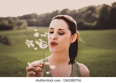 Young woman is blowing on dandelion in green landscape, in spring day.