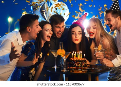 Young woman blowing out candles on her birthday cake with friends in club