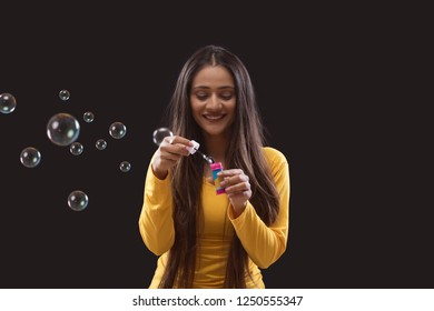 Young woman blowing soap bubbles over black background