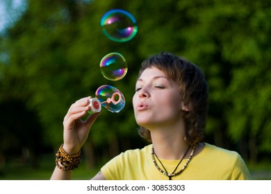 A young woman  blowing up soap-bubbles on the green tree background