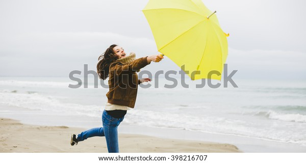 A young woman is blown away with her yellow umbrella on a beach