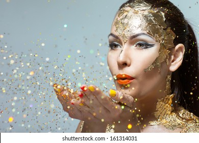 young woman blows with her �¢??�¢??hands sequins.