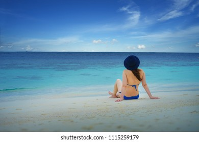 Young woman in blue bikini and blue hat relax on the beach over blue clear sky and crystal sea of tropical beach.