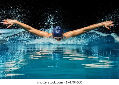 Young woman in blue cap and swimming suit in pool