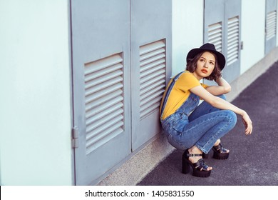 8d6ad1d4e8d850 young woman in blue denim overalls and yellow tshirt with black hat sensual  looking up while