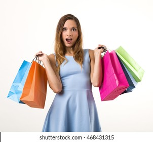 Young woman in a blue dress with colorful shopping bags. White background.