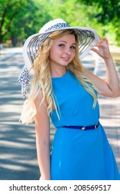 young woman in a blue dress and a hat park