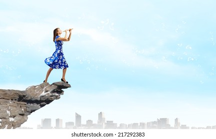 Young woman in blue dress playing fife standing on top of rock