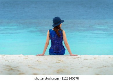 Young woman with blue dress sitting on the beach