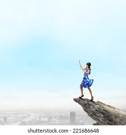 Young woman in blue dress standing on mountain edge
