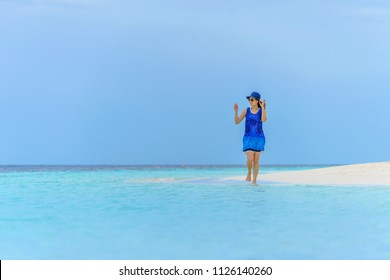 Young woman with blue dress walking on the beach over clear blue sky