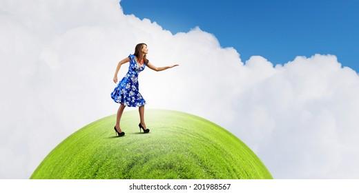 Young woman in blue dress walking on green globe