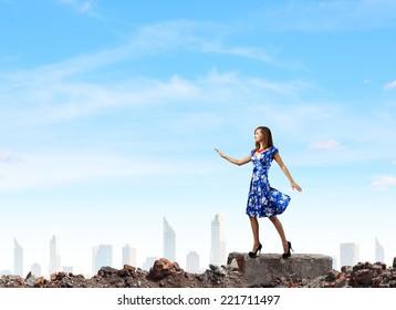 Young woman in blue dress walking among city ruins