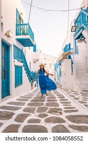 young woman in blue dress and white hat at the Colorful Streets of Mykonos with blue balcony and stairs, Mykonos town Greece