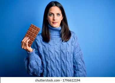 Young woman with blue eyes holding sweet chocolate bar standing over isolated background with a confident expression on smart face thinking serious
