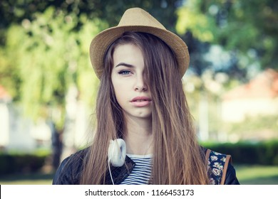Young woman with blue eyes and long hair, headphones and hat, outdoors in park. Closeup portrait, no retouch, greenish filter applied, natural lighting.