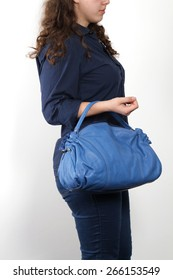 Young woman with blue genuine leather bag isolated on white background