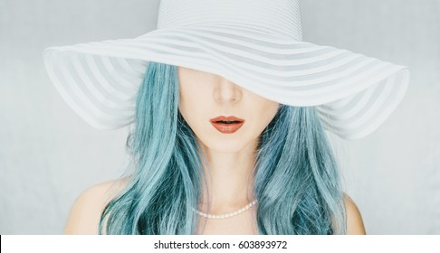 Young woman with blue hair in a hat with wide brim, fashion and beauty.