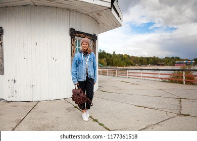 Young woman in blue jeans coat, knitting hat, jeans walkin along the pier with an old lighthouse along the sea . Concept of autumn  holidays at village  and live style