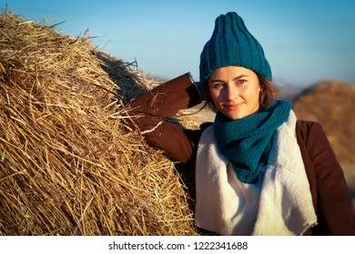 A young woman in a blue knitted hat, brown coat and bluesses enjoys autumn, poses and smiles around haystick and blue wall. The concept of livestyle and outdoor recreation in autumn