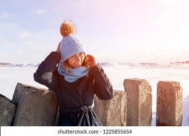 A young woman in a blue knitting hat,  black coat  enjoys winter nature, walking on the frozen sea at the north pole around blue sky. The concept of livestyle and outdoor recreation in winter