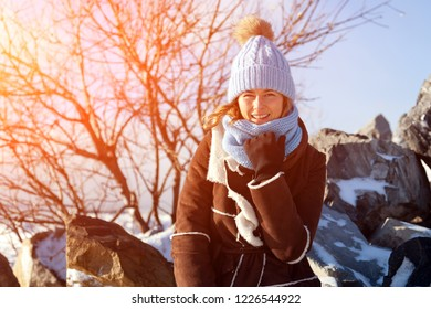 A young woman in a blue knitting hat,   brown coat  enjoys winter nature, sitting on the  stone at the north pole around blue sky in winter frosty day. The concept of livestyle and recreation