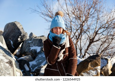 A young woman in a blue knitting hat,   brown coat  enjoys winter nature, sitting on the  stone at the north pole around blue sky in winter frosty day. The concept of livestyle