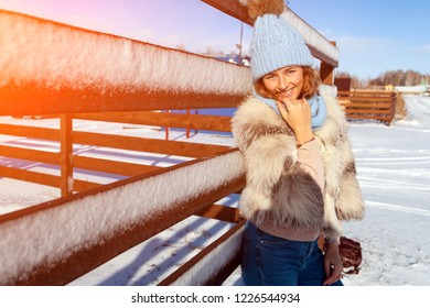 A young woman in a blue knitting hat, white fur coat  enjoys winter nature, posing around fence, walking on  village around blue sky in winter frosty day. The concept of livestyle