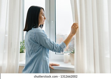 Young woman in blue shirt opening curtains looking out the window in the morning in the room, cloudy day in the city.