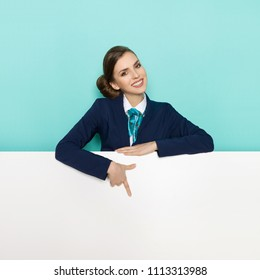 Young woman in blue suit and turquoise scarf standing behind white banner, looking at camera, smiling and pointing. Studio portrait shot on turquoise background.