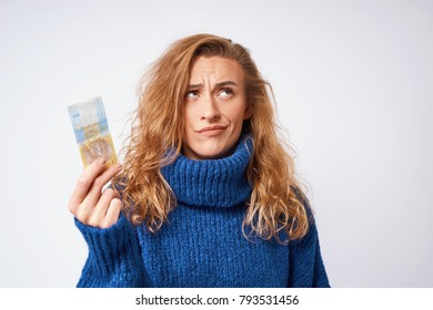 A young woman in a blue sweater wonders at the money, one hryvnia, holding them in her hands against a gray background.