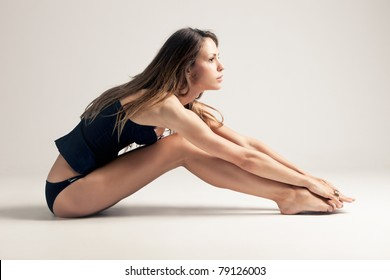 young woman in blue underwear sit on the floor, side view, studio shot, little amount of grain added