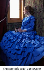 Young woman in blue vintage dress late 19th century sitting in coupe of retro railway train, looking out the window and drinking tea