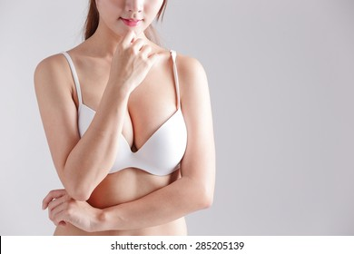 young woman body chest breast with bra and she think about something isolated on gray background, asian beauty