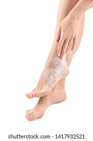 Young woman with body scrub on her legs against white background