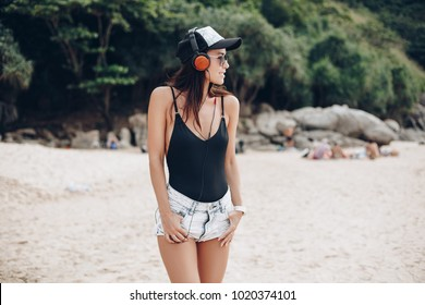 young woman in bodysuit listening music with headphones at beach