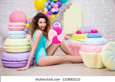 young woman in bodysuit posing with giant pastry decorations