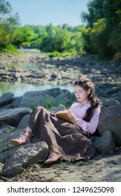 Young woman in a Boho style clothes is reading book in seclusion on the river bank.