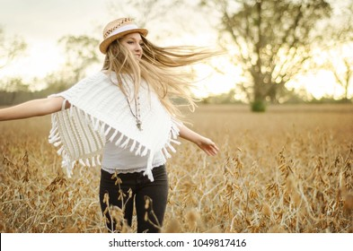 young woman boho style twirling at sunset