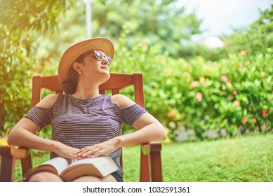 Young woman with book sitting on chair in green garden terrace