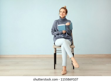 Young woman with book sitting on chair near color wall