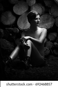 Young woman in boots, sitting at a stack of wood