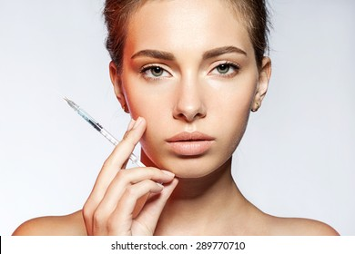 Young woman with Botox injections in the syringe on white background