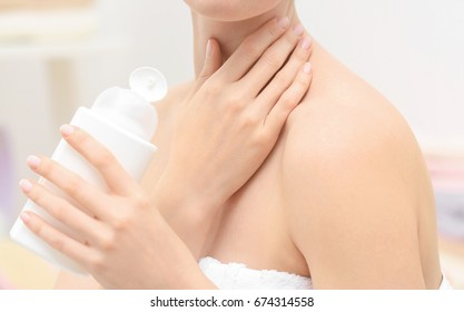 Young woman with bottle of cosmetic product in bathroom, closeup