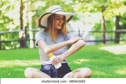 Jeune femme, une bouteille de soleil à l'extérieur, un jour d'été
