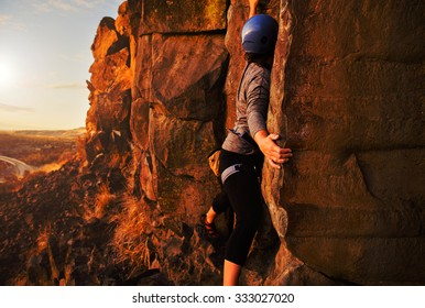 young woman bouldering and rock climbing on large cliffs during sunrise or sunset with a toned overlay filter