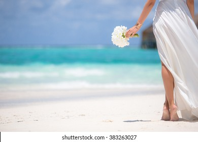 Young woman with bouquet of flowers on the beach.