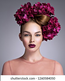 Young woman with a bouquet of purple flowers  in her hair. Girl with a creative hairstyle and blossoming flowers.