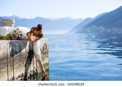 Young woman with bouquet touching water. Horizontal