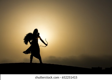young woman with a bow and arrors in a desert near Dubai
